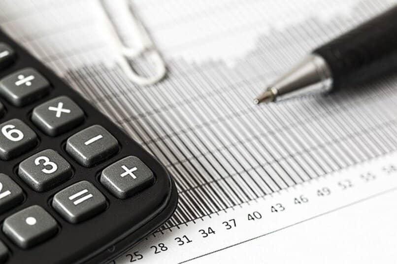 Calculadora junto a lapicero anotando en papel
