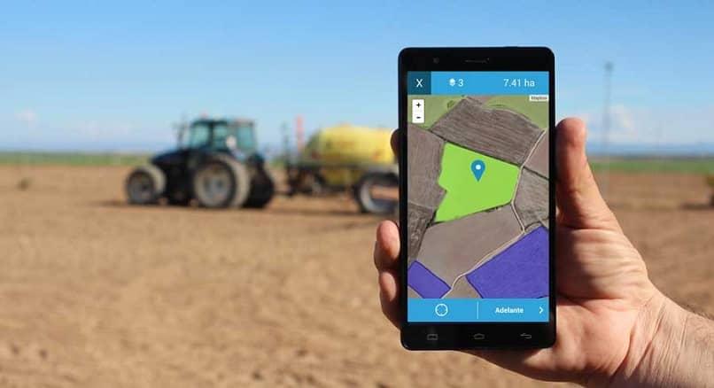 movil con aplicacion para medir terreno abierta y de fondo un terreno con granja y excavadora