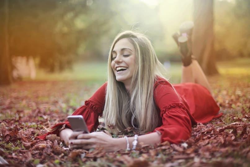 chica acostada sobre hojas revisa telefono