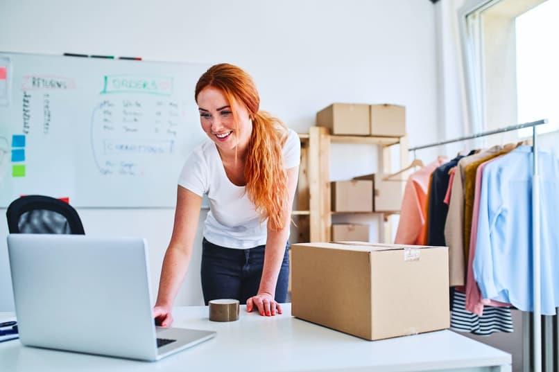mujer con cajas y computadora