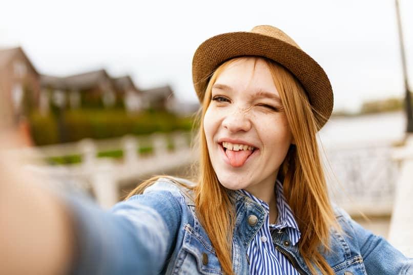 mujer con sombrero se toma selfie