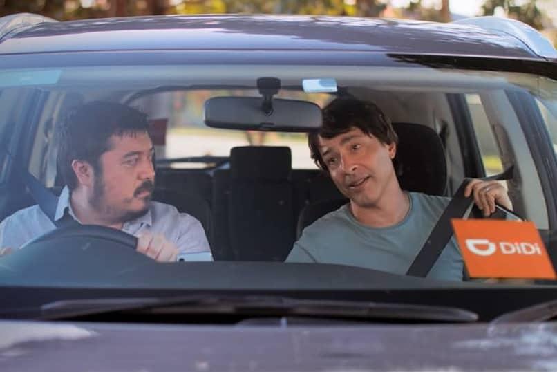 conductor de coche didi con un hombre manejando y uno en el asiento que es el pasajero