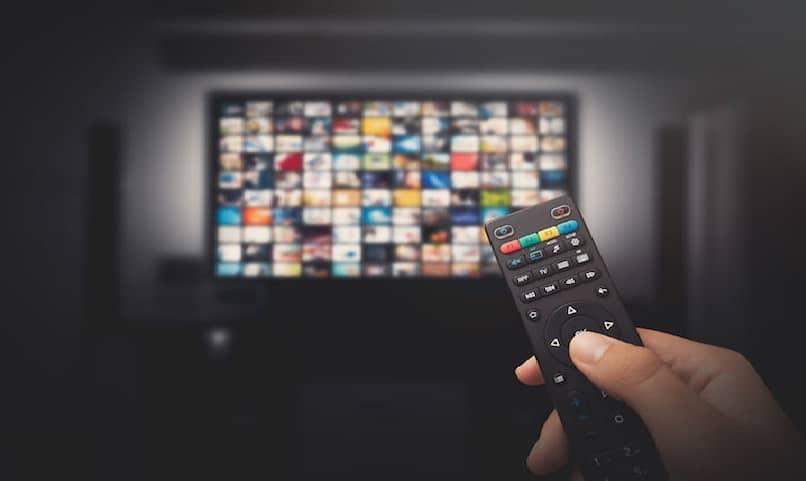 mano con control remoto para ver tv y controlar canales