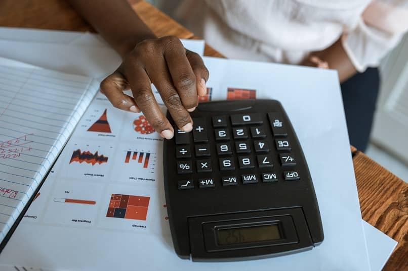 personal revisando tablas de inversiones con una calculadora