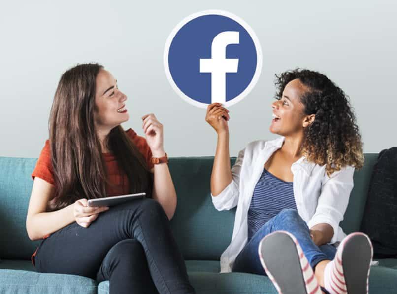 dos mujeres sosteniendo el logo de facebook