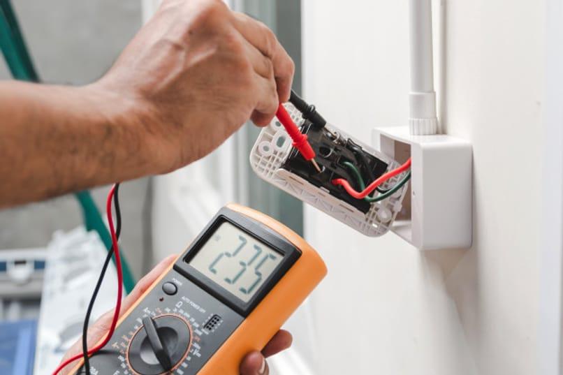 persona midiendo el voltaje electrico