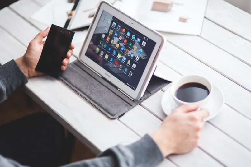 persona utiliza tableta android y sostiene taza de cafe