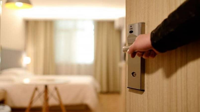 hombre abriendo la puerta de su habitacion en un hotel