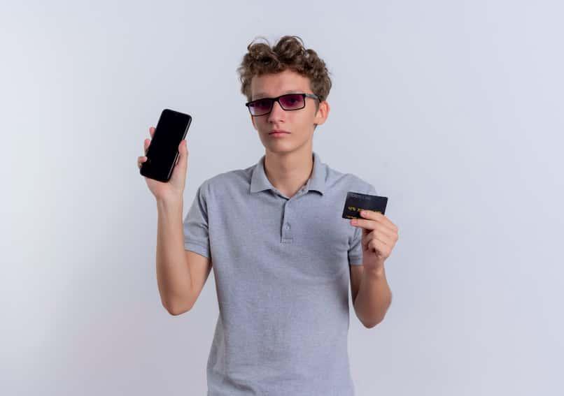 hombre sosteniendo la tarjeta de credito y el telefono
