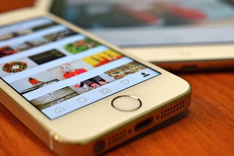 iphone y tablet con app de instagram sobre escritorio