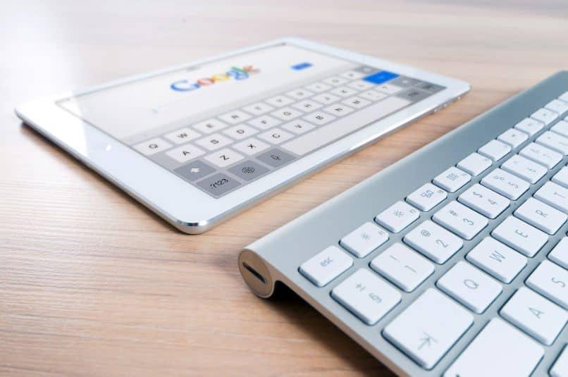 ipad con pagina de google y teclado sobre mesa