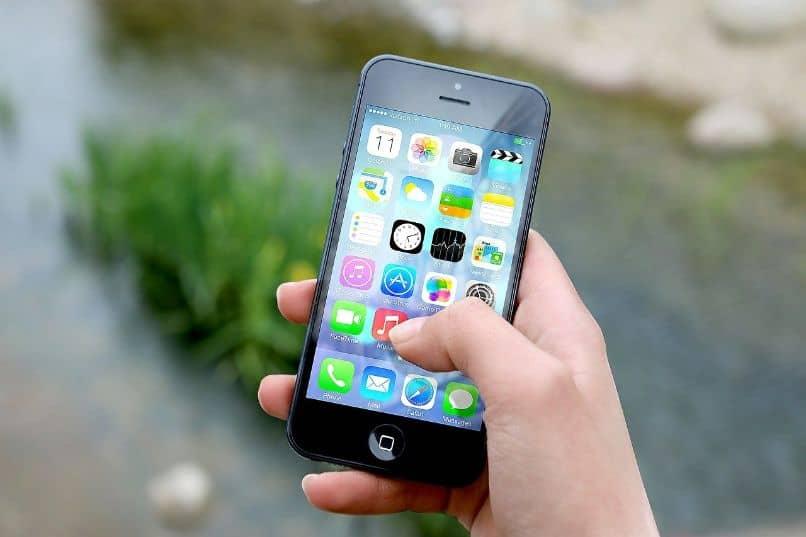 iphone en mano sobre fondo lluvioso