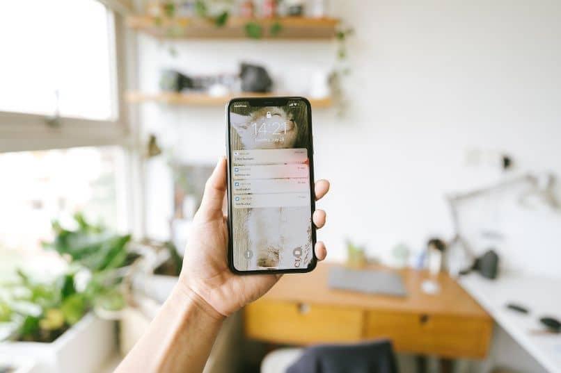 iphone en mano sobre oficina