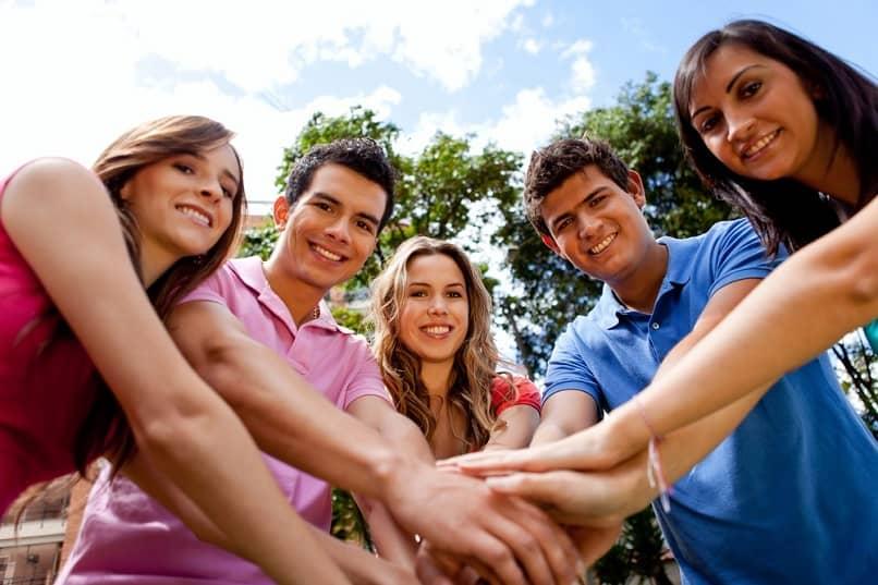 grupo jovenes juntar las manos equipo
