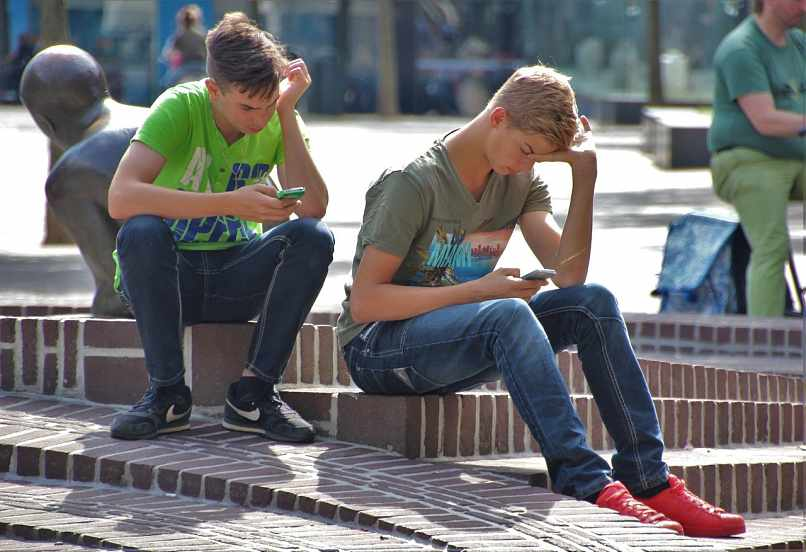 chicos sentados en una plaza con moviles