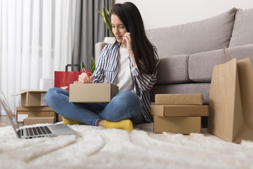 mujer sentada escribiendo en una caja