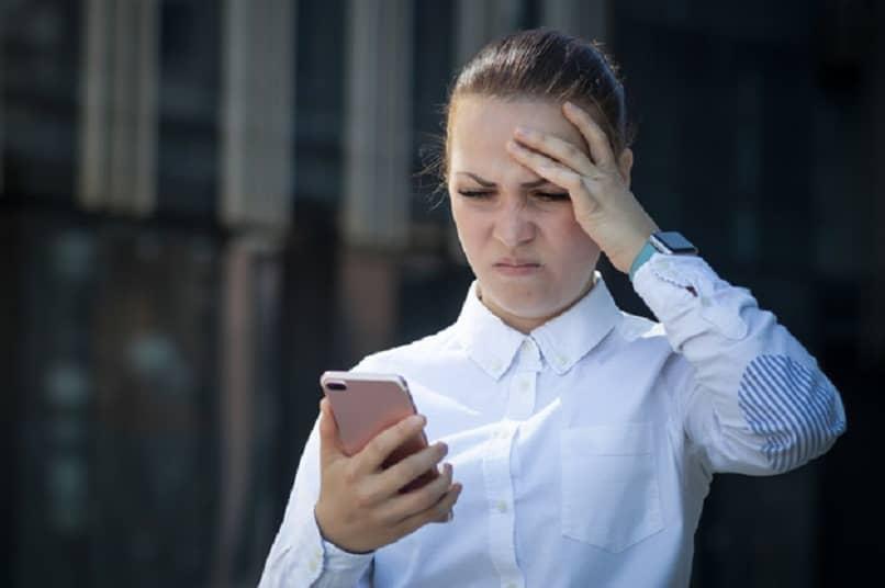 mujer frustrada viendo su celular