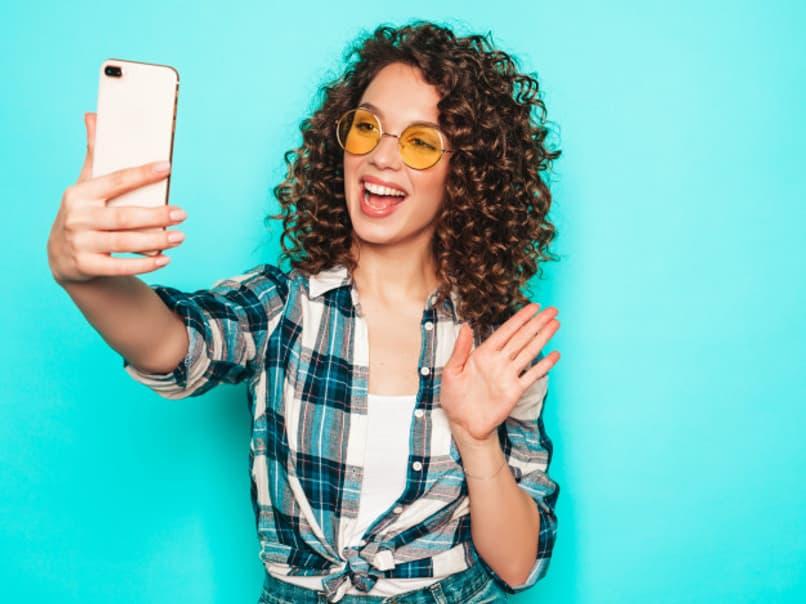 mujer joven saludando la camara del telefono