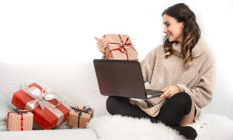 mujer sentada con una computadora y regalos
