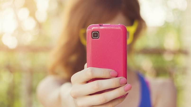 mujer utiliza telefono rosado