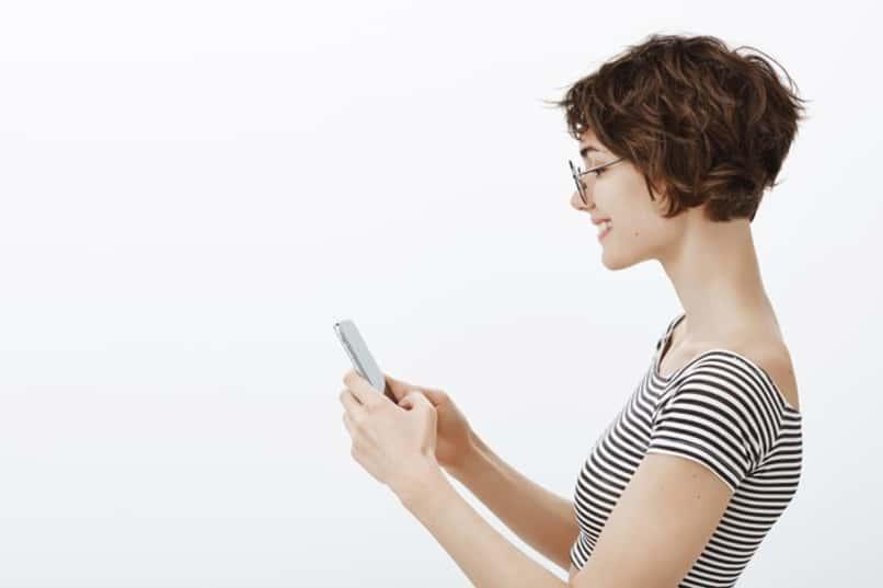 mujer sonrie mientras usa telefono