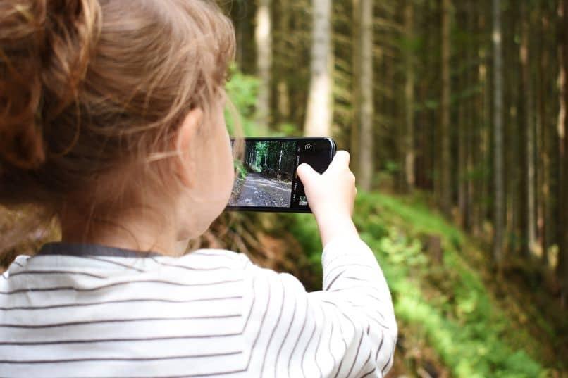 nina con celular tomado foto en bosque