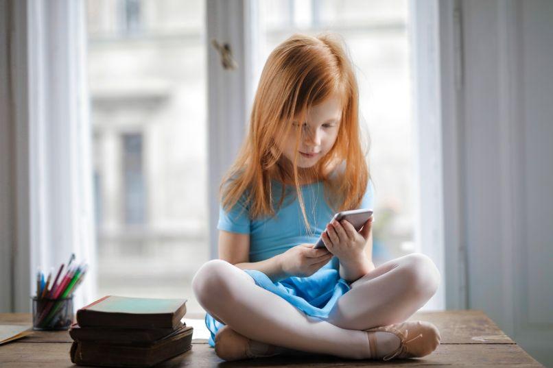 nina utilizando celular iphone