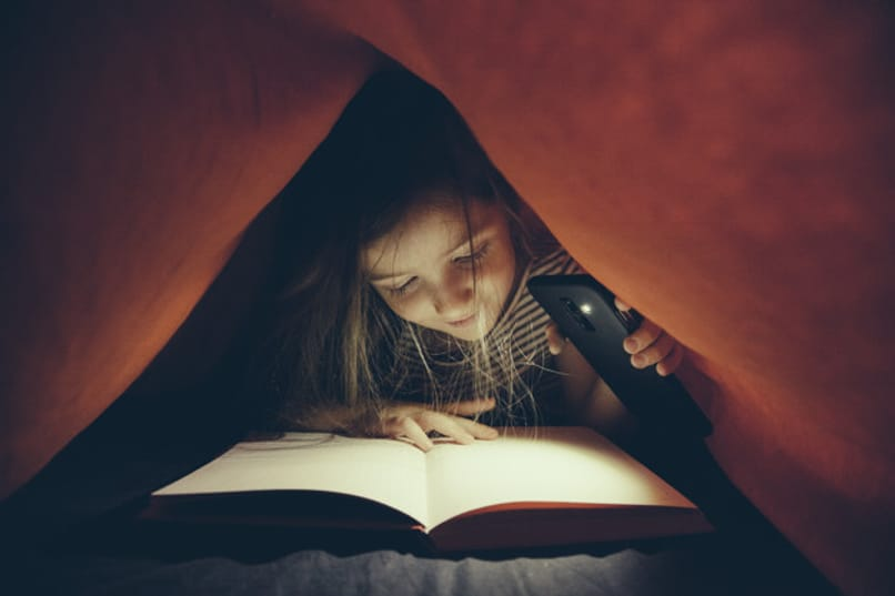 nina lee libro alumbrando con linterna de telefono