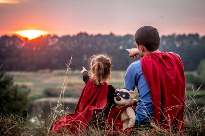 padre e hija disfrazados de superheroes senalando el horizonte