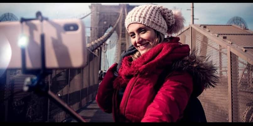 mujer fotografiandose con baston de selfie