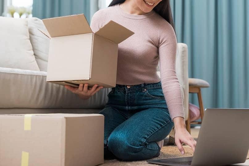 mujer con paquetes consultando en pc