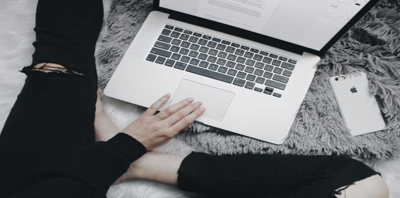 mujer con laptop y telefono