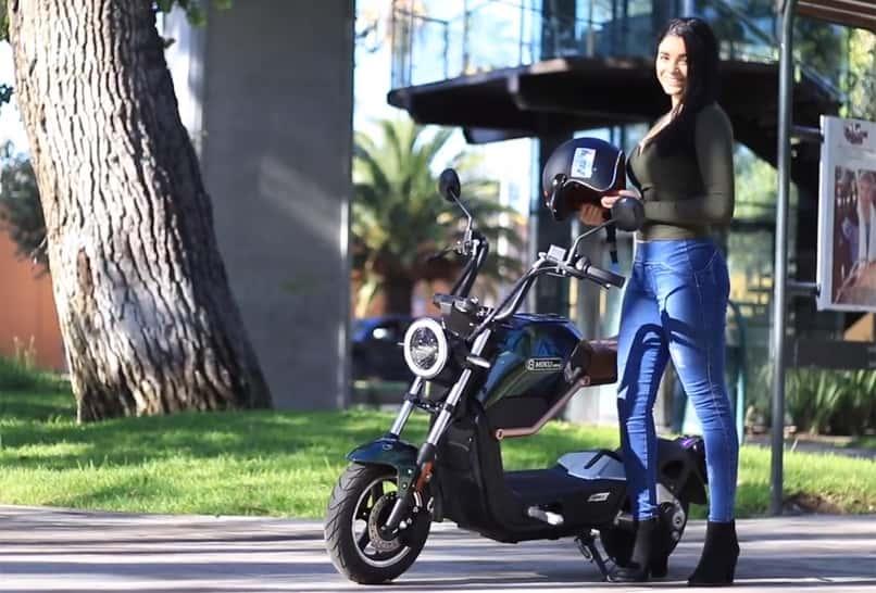 chica de pie junto a scooter