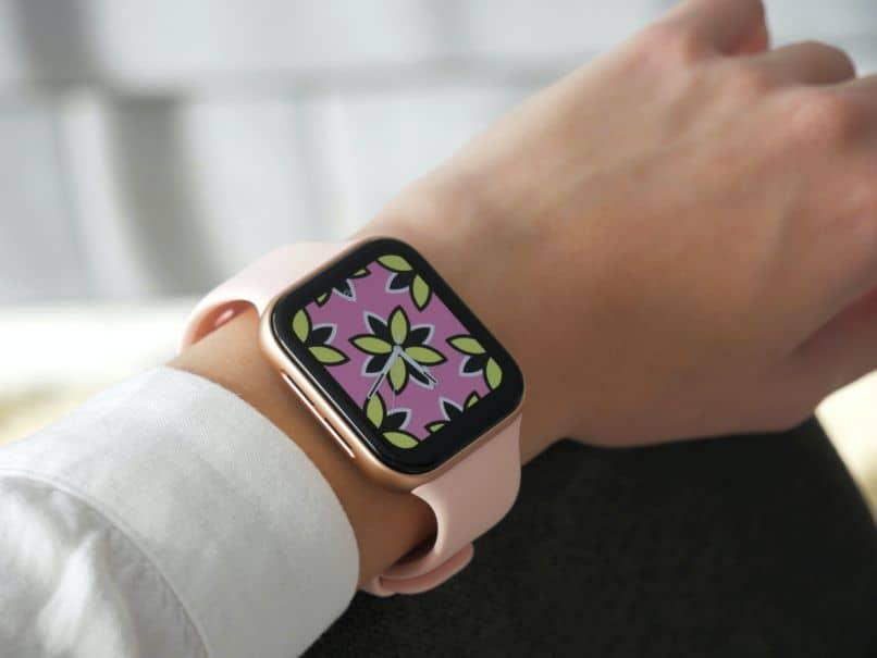 chica con smartwatch rosado en la mano