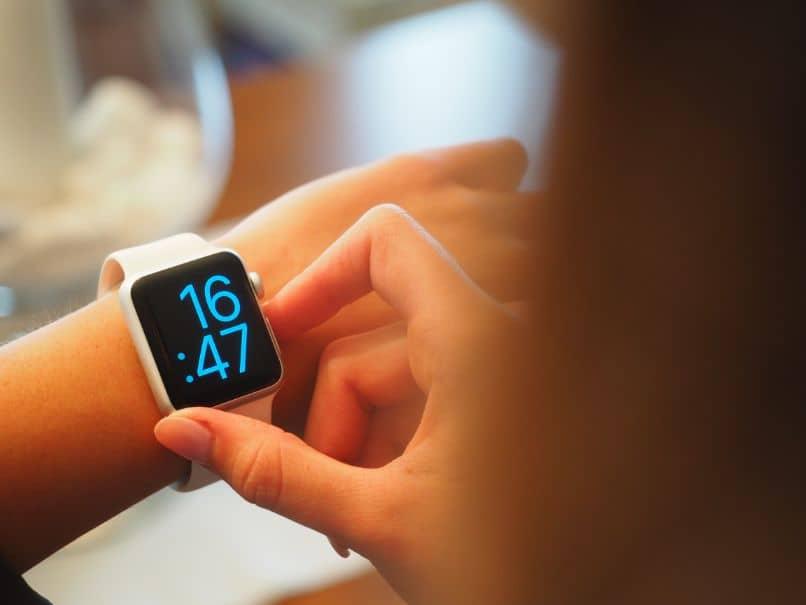 smartwatch rosado en manos de chica