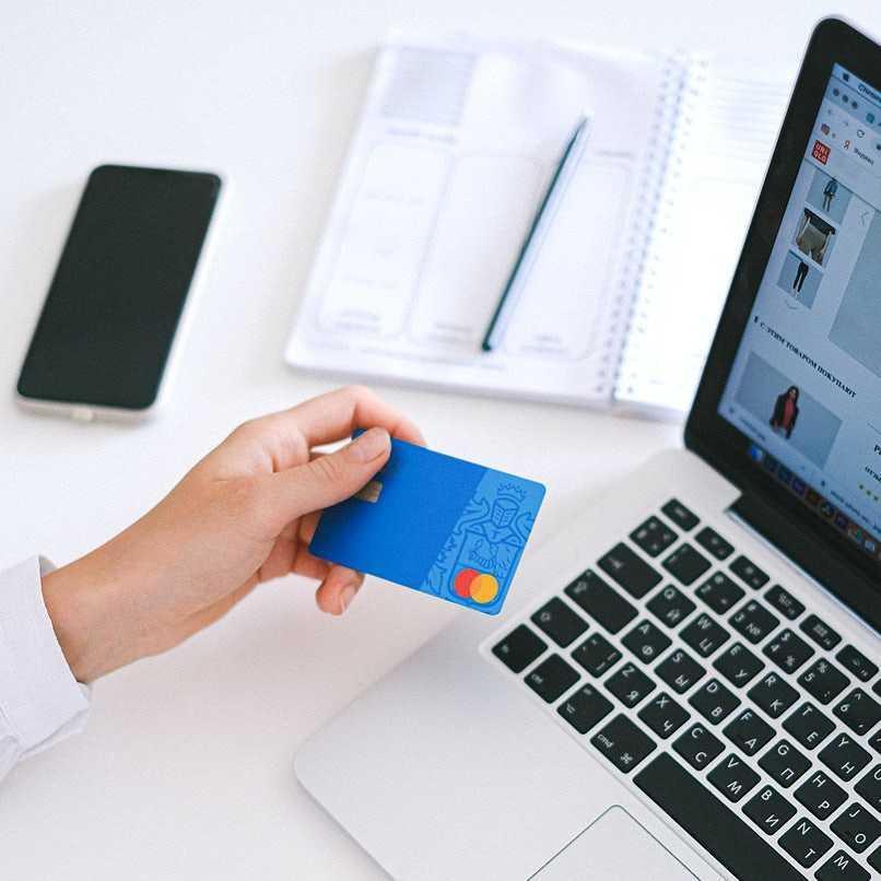 persona con tarjeta bancaria y laptop