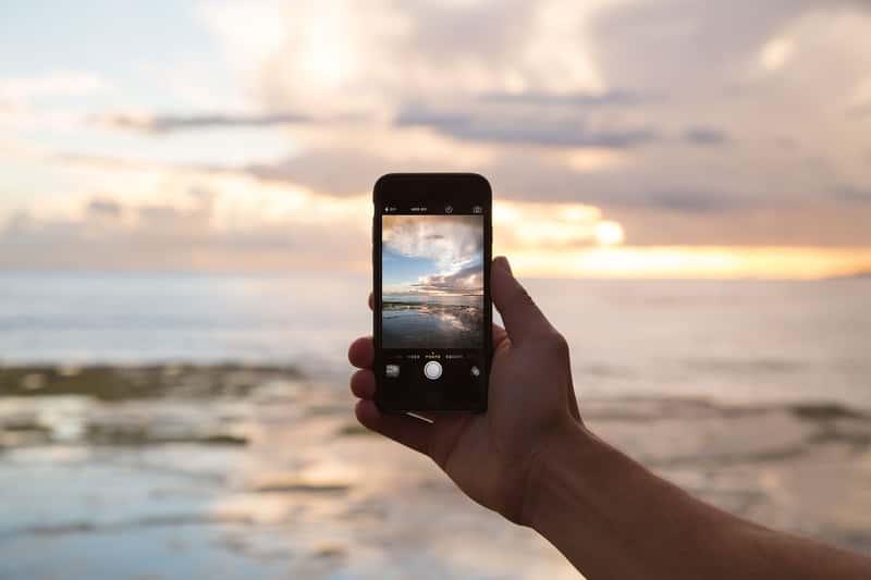 telefono fotografiando el horizonte y el sol