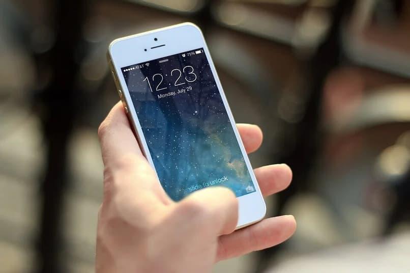 mano sostiene telefono iphone