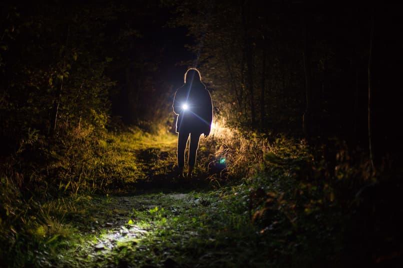 persona alumbra en la oscuridad